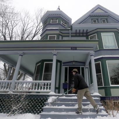 Jim Rodda shovels his front porch in Appleton as cold,