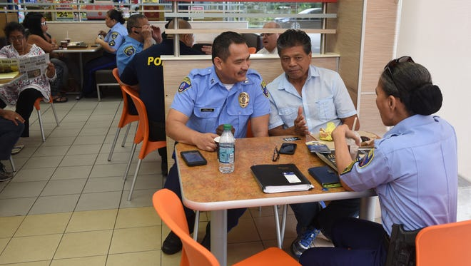 In celebration of National Coffee with a Cop Day, Guam Police Department officers spend part of their morning conversing with island residents over a cup of coffee at the McDonald's restaurant in Yigo on Oct. 4, 2017.