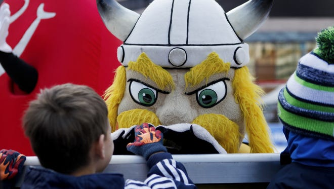 Captain Victor E. Viking of NKU greets Caleb Heeg, 6, before the annual Mascot Broomball game on Fountain Square Saturday, January 17, 2015. Viking's team Super Sweepers were defeated by Legion of the Broom.