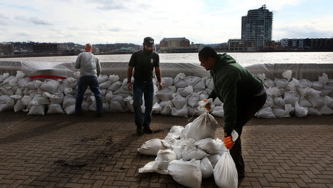 Cincinnati City Parks workers (from right) Calvin Lockett, Garrett Dienno and Ken Holloway, add sandbags by Montgomery Inn Boathouse where the rising water of the Ohio River is nearing the sidewalk.