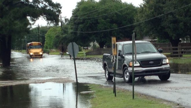 Cars drive along a flooded Cankton Road in Carencro after a storm system dumped about 9 inches of rain on the area.