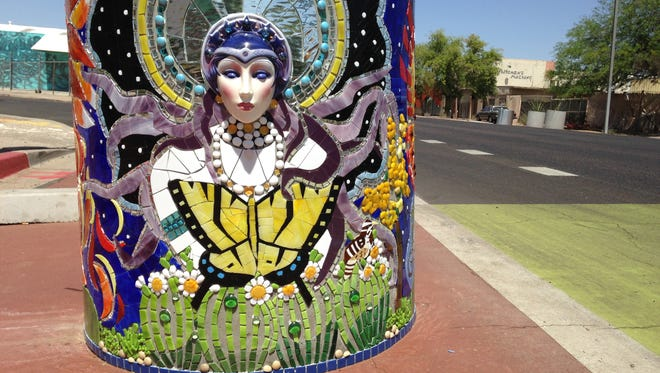 "Tammi Lynch Forrest has traveled the world creating mosaics, but this was her first opportunity to create a public piece in her home state. The planter features two faces, what her friends are calling the ""the Arizona goddesses"" depicting the sun and the moon. In between, Forrest includes the state butterfly — the two-tailed swallowtail butterfly — and our state snake, the ridge-nosed rattler."