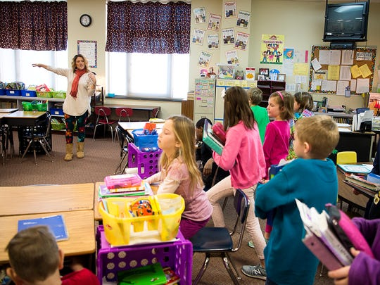 Third grade teacher Shelley Watts instructs her students where to sit down during a two-hour delay schedule Monday at Fletcher Elementary School.