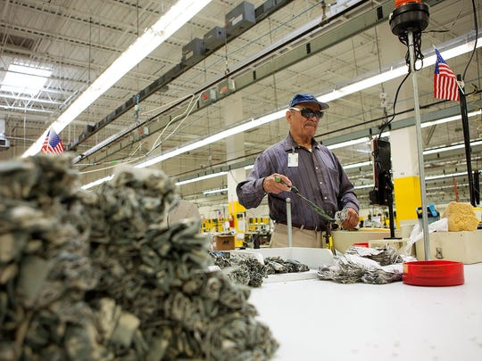 Eduardo Moncayo, a blind worker in ReadyOne Industries' not-for-profit factory in East El Paso, works on military uniform sleeve tabs.