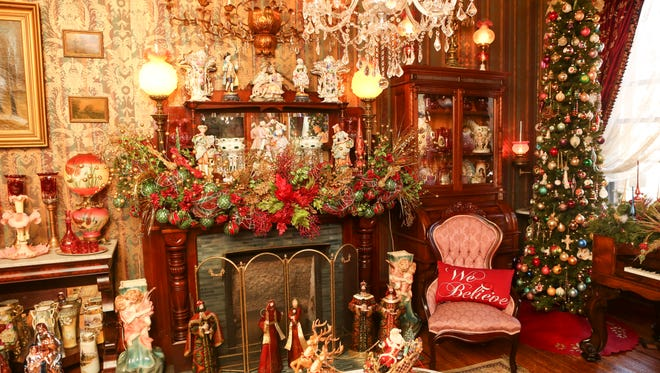 The formal living room at the home of David Brown in Old Louisville has full Christmas decor with Victorian chairs flanking the ornate fireplace and a chandelier with medallion. Nov. 19, 2015