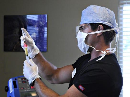 Dr. Joel Baumgartner prepares for a stem cell treatment