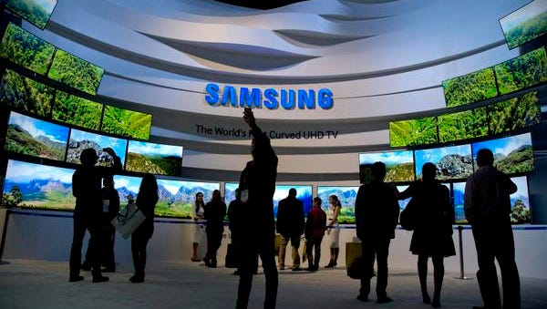Trade show attendees take in a display of Samsung curved UHD TVs at the International Consumer Electronics Show, Thursday, Jan. 9, 2014, in Las Vegas. (AP Photo/Julie Jacobson)