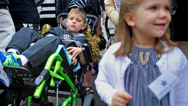 Vanderbilt fan Michael Sloan, 6, left, waits to see players and coaches at the Star Walk prior to the kick off against Massachusetts on Saturday, Sept. 13, 2014.