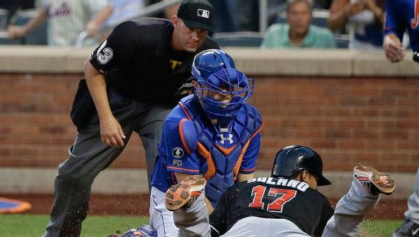 Mets catcher Travis d'Arnaud tags out the Miami Marlins' Donovan Solano at the plate as he tries to score from first base on a double in the fourth inning Friday.