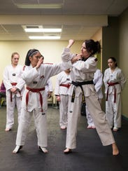 """Darci Miranti practices self-defense techniques with Louise Lluisma, 14, during class at Big Sky Taekwondo. Miranti's goal """"is to be a good leader and role model for the girls. Girls don't always get good role models in activities they're taking part in."""""""