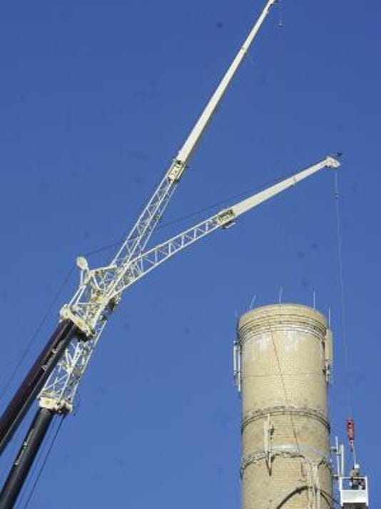 Two cranes reach a height of about 180 to work on a smokestack in York city.  YORK DAILY RECORD/SUNDAY NEWS--JASON PLOTKIN