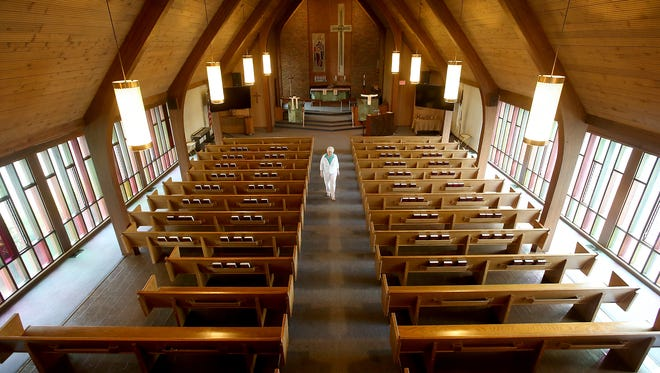 Nancy VanBuskirk, financial secretary for Community of Christ at Memorial Lutheran, walks down the aisle of the sanctuary at the Bremerton church on Thursday.