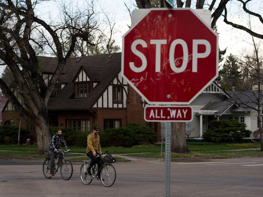 Cyclists cruise through the intersection of West Oak Street and Jackson Avenue on Tuesday, May 1, 2018, in Fort Collins, Colo.