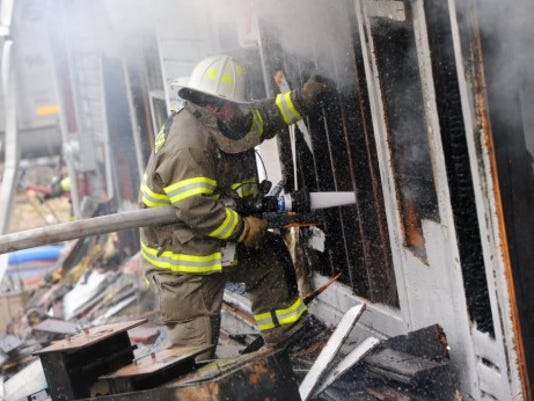 A firefighter battles along the side of a home on fire in Newberry Township on recently. Jason Plotkin - Daily Record/Sunday News