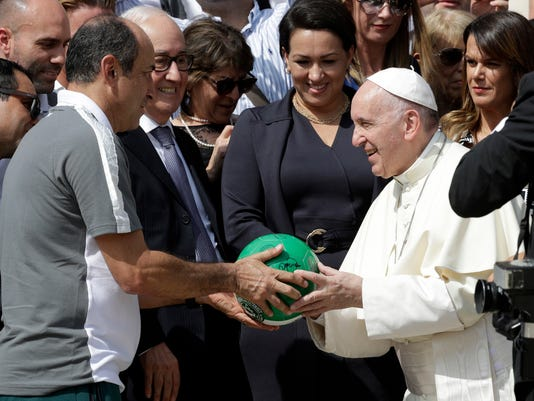 Pope Francis is given a signed soccer ball by members of the Chapecoense soccer team, at the end of his weekly general audience, at the Vatican, Wednesday, Aug. 30, 2017. Chapecoense will play AS Roma on Thursday in a charity match to raise funds for the team following last year's plane crash in Colombia where only three players of the 77 passengers on board survived. (AP Photo/Andrew Medichini)