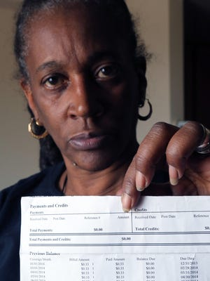 Martha Holcomb holds her health insurance statement showing she paid the 33 cent-per-month premium. She said she questioned the very small amount but was told that was the amount she owed. She ended up having $770 deducted from her tax refund because her premium should have been higher.