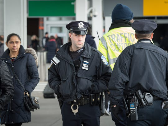 A Port Authority police officer looks on as protesters gather in New York at JFK International Airport's Terminal 4 on Jan. 28, 2017.
