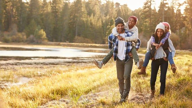 Parents Giving Children Piggyback Ride On Walk By Lake