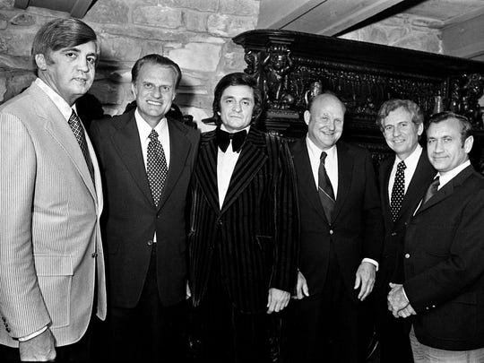 The conversation had to be lively when these distinguished guests gathered at the home of Johnny and June Carter Cash on Old Hickory Lake for dinner Oct. 26, 1973. They are Buford Pusser, Dr. Billy Graham, Cash, John Rollins, Dr. Nat Winston and James F. Neal.