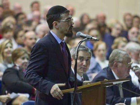 Rabbi Moshe Gourarie speaks before a big crowd in December