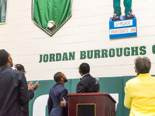 Olympian Jordan Burroughs (left) and Winslow Superintendent H. Major Poteat look at the wrestler's name on a gym wall at Winslow High School in September 2016.