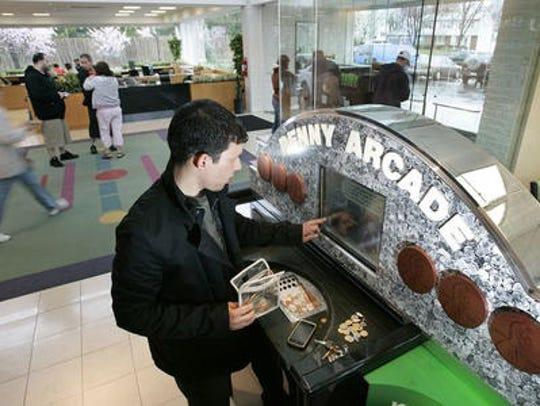 A consumer uses a TD Bank Penny Arcade machine, now