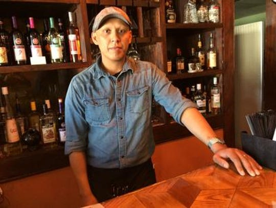 Edgar Carbajal stands behind a bar he made inside his