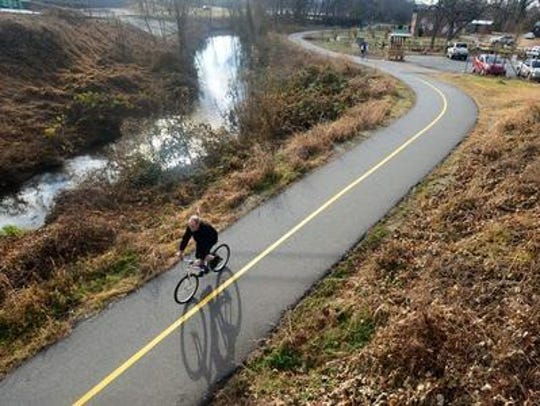 A man rides a bike on the Swamp Rabbit Trail.
