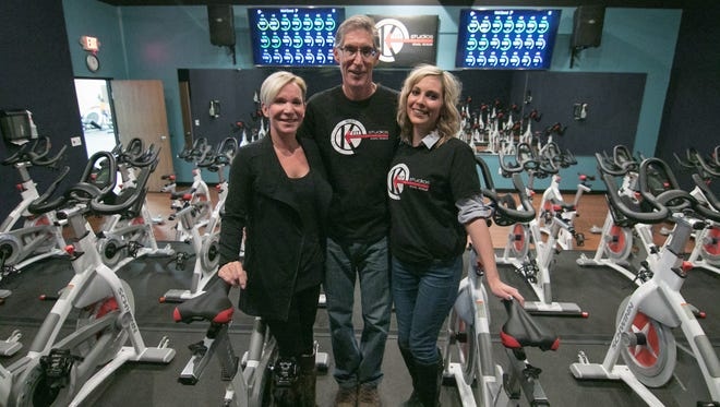 Shown from left Wednesday, Dec. 13, 2017, KFit Studios owners Kelly and Jeff Fletcher, and their daughter Jamie Fletcher, who manages the workout facility, show off the Rev X studio which has 34 bikes wirelessly connected via cloud network and then back to the monitors in front of the studio that display real-time leaderboard stats on the participants in the class.