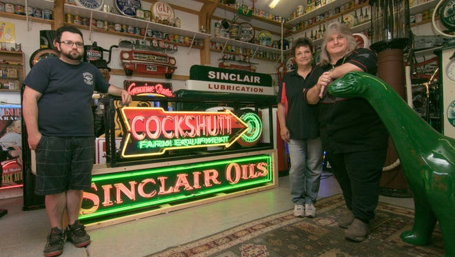 From left, Branden Jarvis and his parents Dawn and Terry Hubert, shown Tuesday, June 12, 2018, run Big Cheese Productions from their Brighton Township home, restoring signs, vintage gasoline pumps and other antiques.