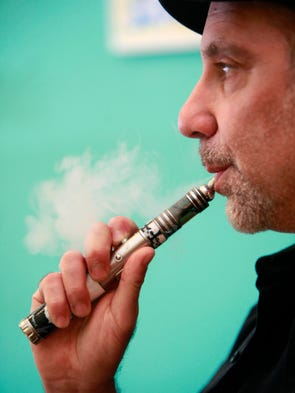 Rob Sands, owner of Palm Beach Vapors on Campbell Avenue, exhales vapor from an e-cigarette.