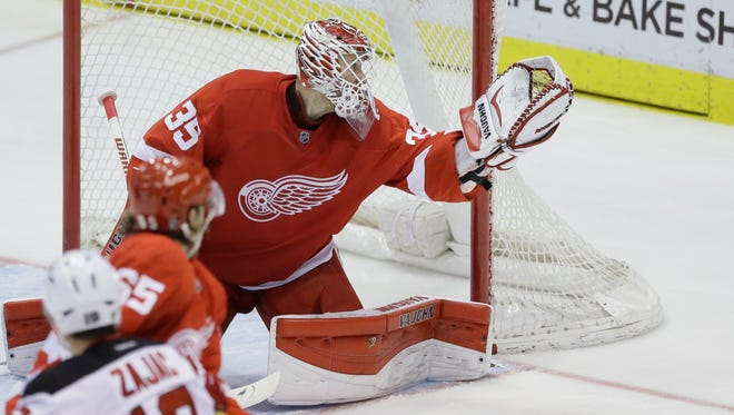 Detroit Red Wings goalie Jimmy Howard makes a save against the New Jersey Devils in Detroit on Dec. 31, 2014.