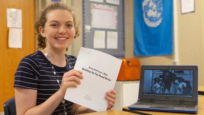 "Allison Reed, Washburn Rural Middle School eighth grader, holds up materials Tuesday from her presentation entitled ""All the World Loves a Baby: Breaking the Two Pound Barrier,"" which placed first at National History Day in the Individual Documentary competition."