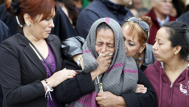 Agapita Montes-Rivera, center, mother of Antonio Zambano-Montes, is comforted following the funeral for her son Feb. 25, 2015, at St. Patrick's Catholic Church in Pasco, Wash.