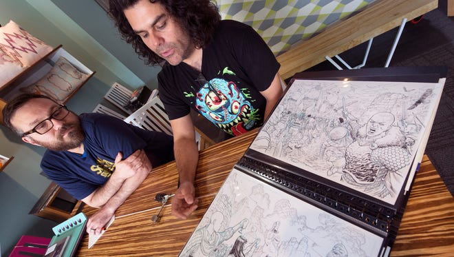 Vito Grippi, left, a founder of Story Supply Co., watches as 'Deadpool' artist Mike Hawthorne shows the sketches he drew for the covers of Story Supply's new line of artist sketchbooks.
