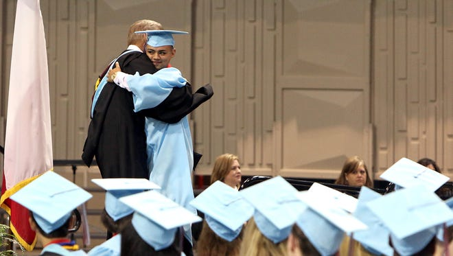 A 2016 graduate hugs Hirschi Principal Doug Albus before walking across the stage to receive his diploma at Kay Yeager Coliseum.