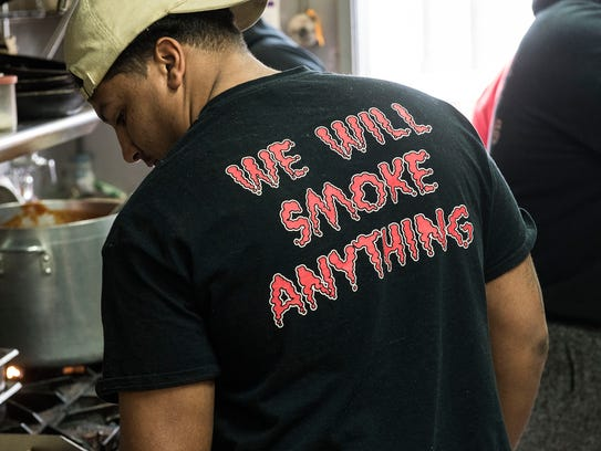 A cook checks on bacon, wearing his 3 Hogs BBQ shirt,
