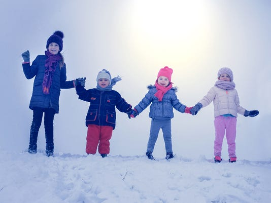 Medium group of  children standing in the snow.