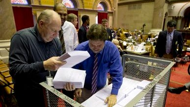 Workers unload budget bills that will be distributed to members' desks in the Assembly Chamber at the Capitol on Tuesday, March 31, 2015, in Albany, N.Y.