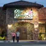 In this May 22, 2014 photo, patrons exit an Olive Garden Restaurant, a Darden restaurant brand, in Short Pump, Va. Darden's fiscal fourth-quarter profit dropped 35 percent, dragged down by charges and costs tied to its strategic plan to reshape the restaurant company. (AP Photo/Steve Helber) ORG XMIT: NYBZ189