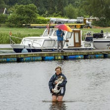 A woman holds a dog in her arms as she walks in the flooded Vecht river following heavy rainfalls, in Ommen, on May 28, 2014. AFP PHOTO/ANP/ LEX VAN LIESHOUT netherlands out        (Photo credit should read LEX VAN LIESHOUT/AFP/Getty Images)