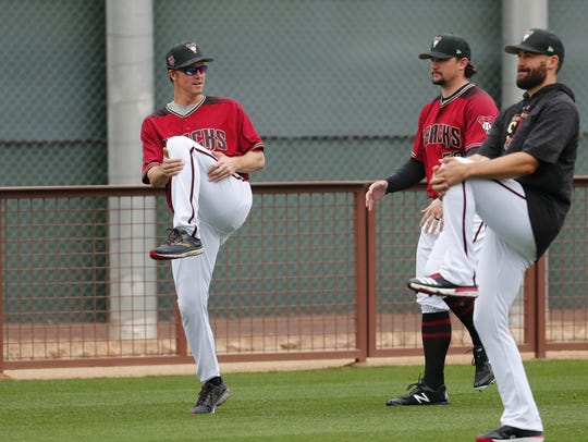 Diamondbacks starting pitcher Zack Greinke (left) warms