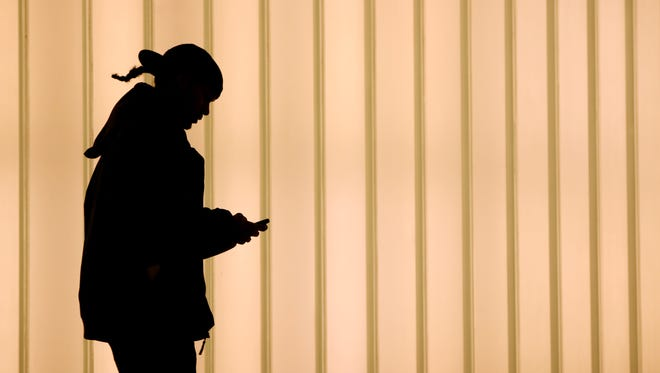 In this November 12, 2010 file photo, a woman texts on her cell photone as she walks inside of the World Trading Center in New York.