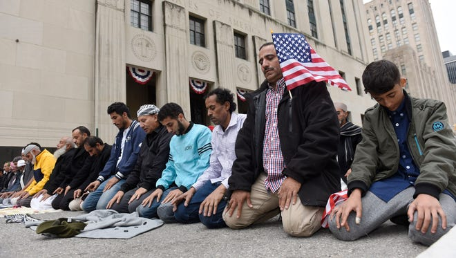 Yemeni-Americans and community members protest the latest version of the Muslim travel ban, saying their daily afternoon prayer in the street in front of the federal courthouse in Detroit.