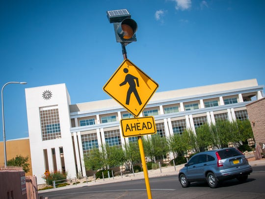 A new, solar-powered, flashing sign warns motorists that pedestrians will be crossing by Las Cruces City Hall.