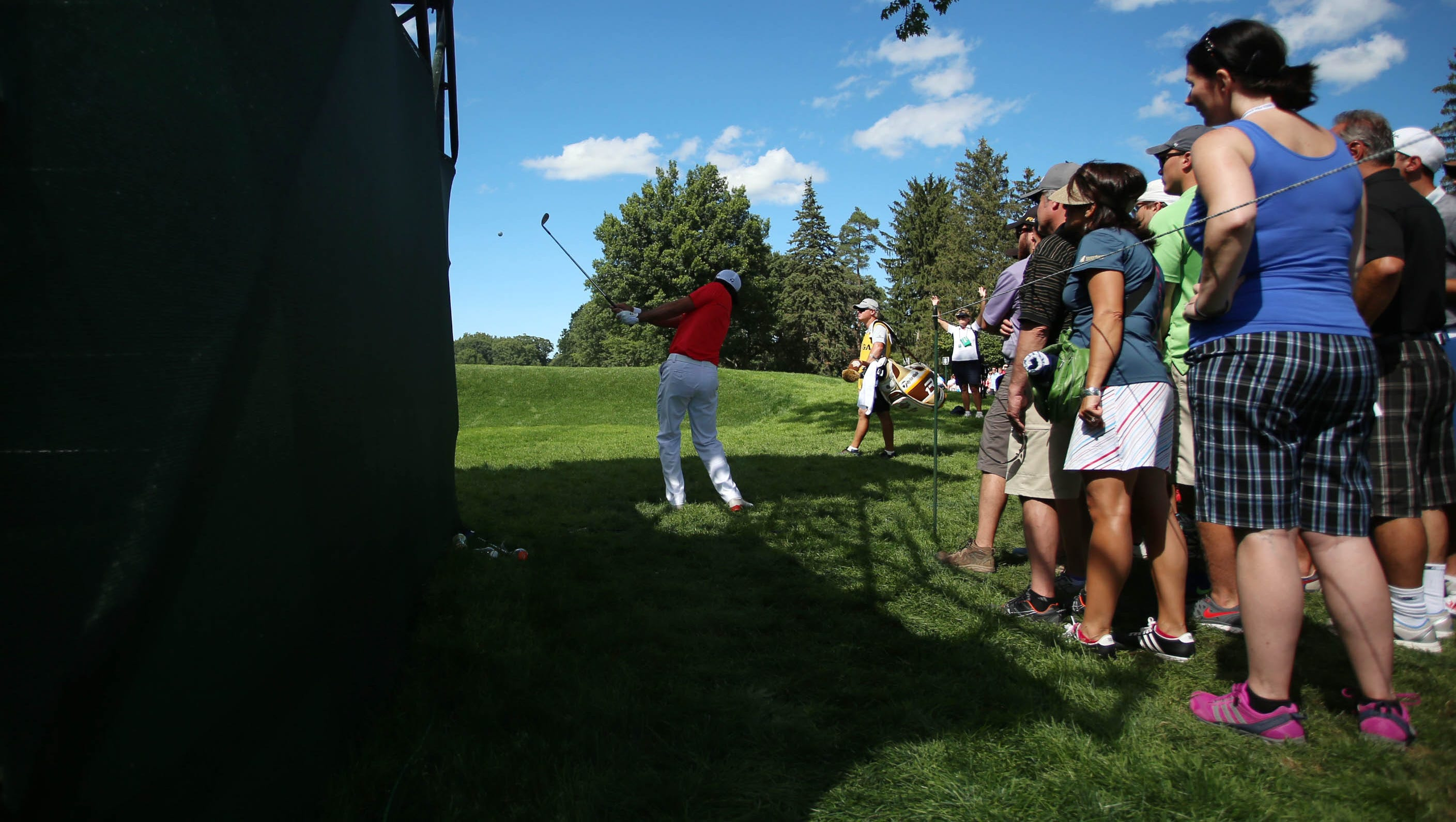 Jason Day plays from the rough near the grandstands on No. 8.
