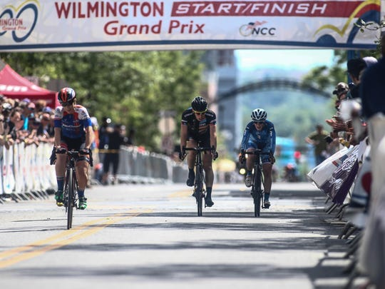 Samantha Schneider, left, of team IS Corp p/b Smart Choice MRI crosses the finish line in front of the Grand Opera House on Market Street to win the Women's Pro, category I & II (25 miles) race Saturday in Wilmington.