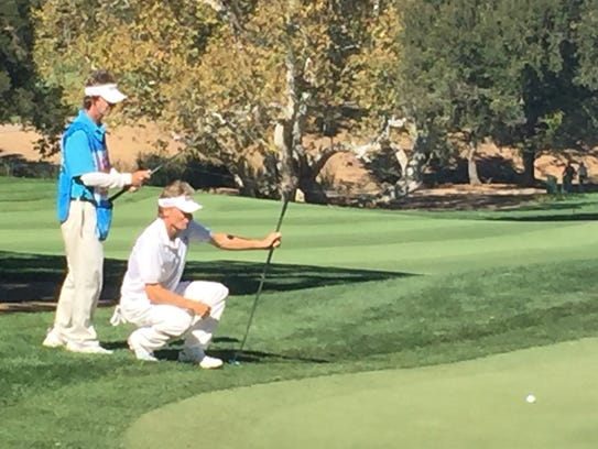 Bernhard Langer lines up a putt with his caddie during