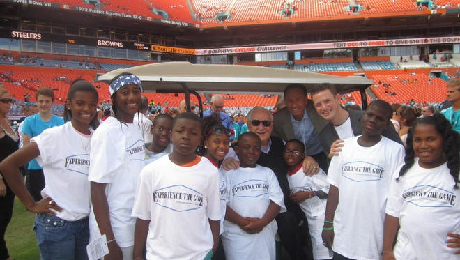 Alex and Michael Sheck with a group of kids at a Miami Dolphins game.