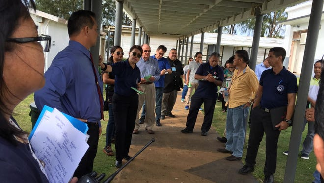 Education officials, along with the Department of Public Works, lead a walk through of Simon Sanchez High School as part of a pre-proposal conference for a new request for proposal for the school's rebuilding project Feb. 2, 2017.